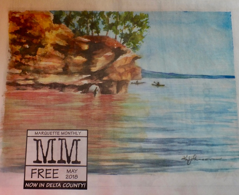 Marquette Monthly magazine cover with red cliffs and water and the letters MM