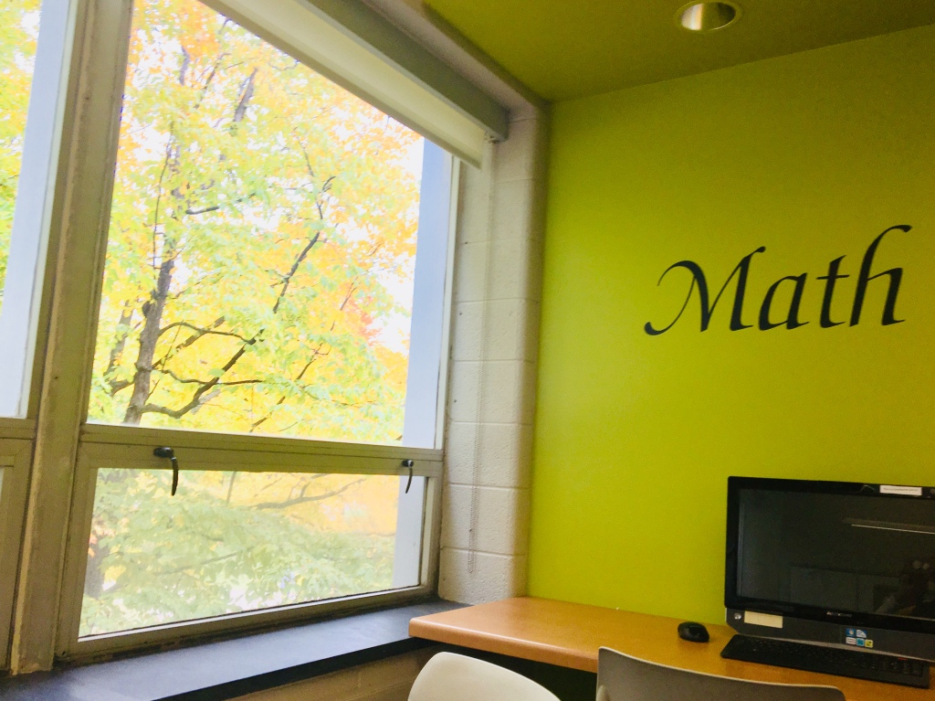 A wall with Math on it and fall foliage outside the windows with a computer on a ledge in a university learning center at Michigan Tech.